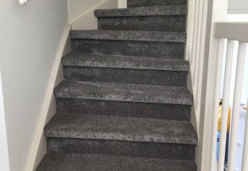 Trap laten stofferen met hoogpolig grijs tapijt